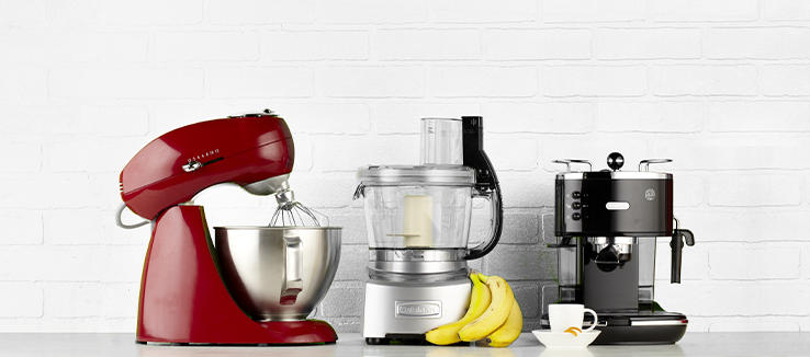 A Mixer, A Food Processor, And A Coffee Machine Sit On A Bar.