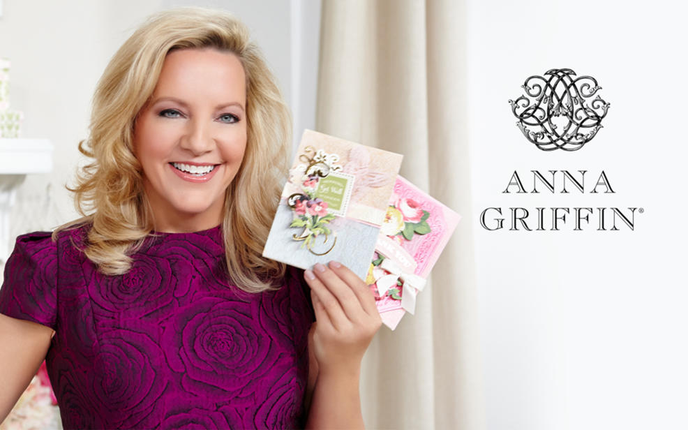 Anna Griffin Logo. Anna holds beautifully decorated handmade cards.