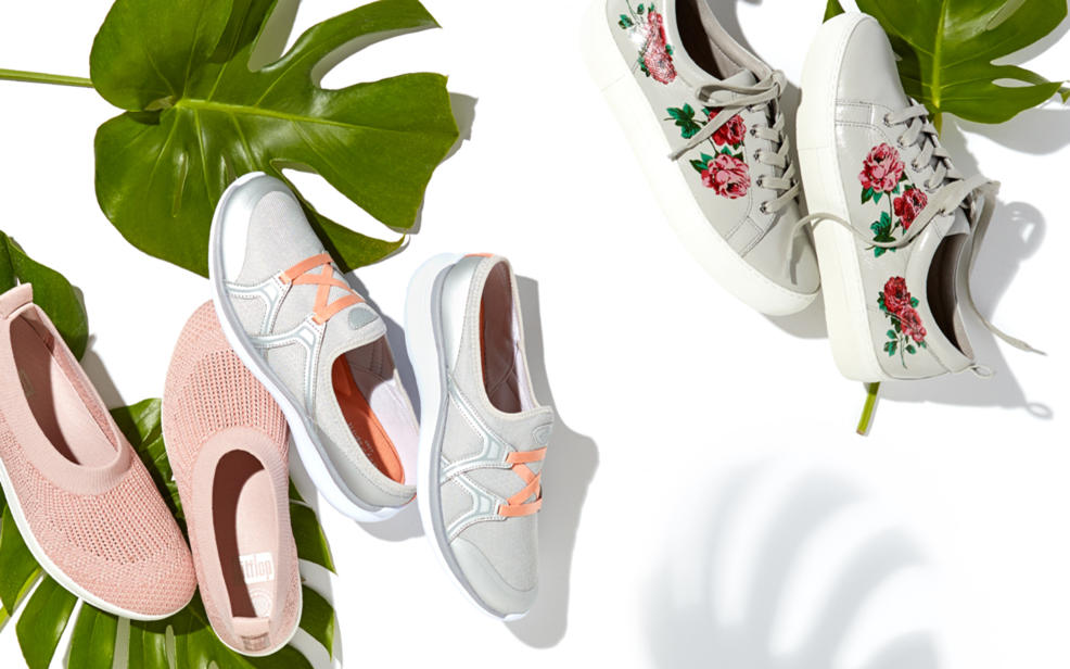 Sneakers and slip-ons dispalyed with tropical leaves