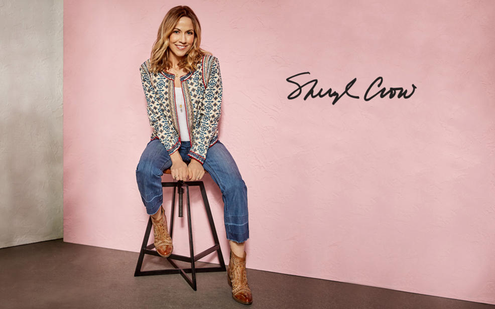 Sheryl Crow sitting on a stool, dressed with a rock-and-roll twist.