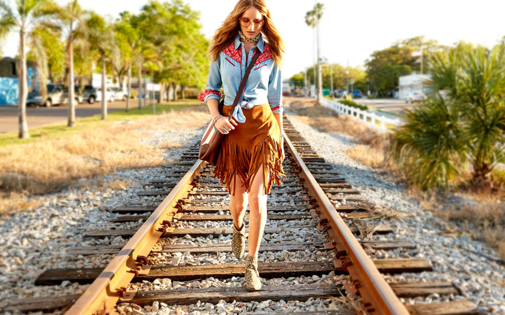 A woman in a fringe skirt and denim shirt walks on railroad tracks.