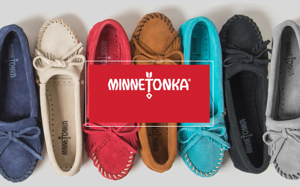 Minnetonka logo: Comfy moccasins, sandals and boots with handcrafted details.