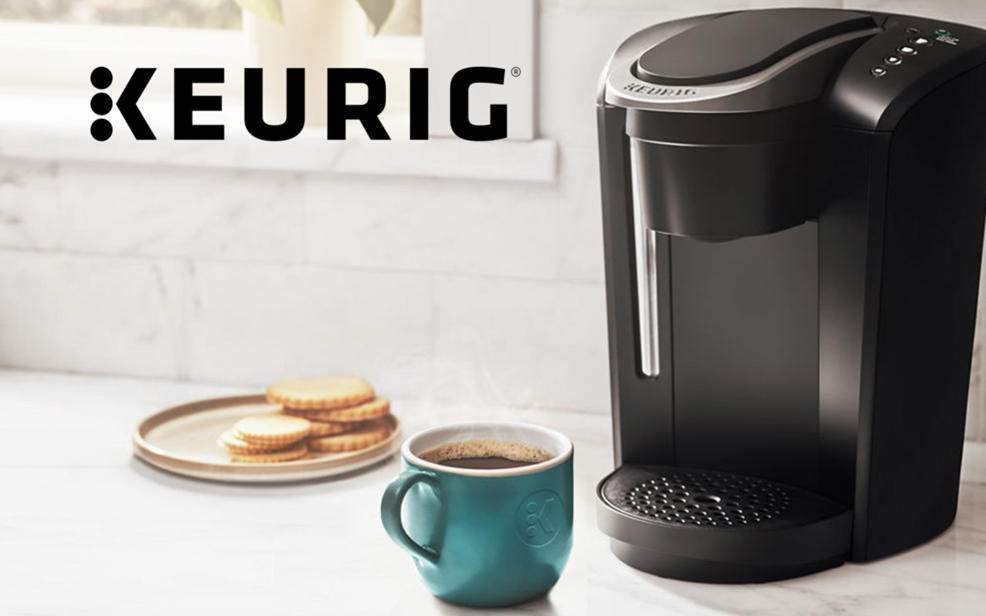 Keurig. a coffee maker and a cup of coffee