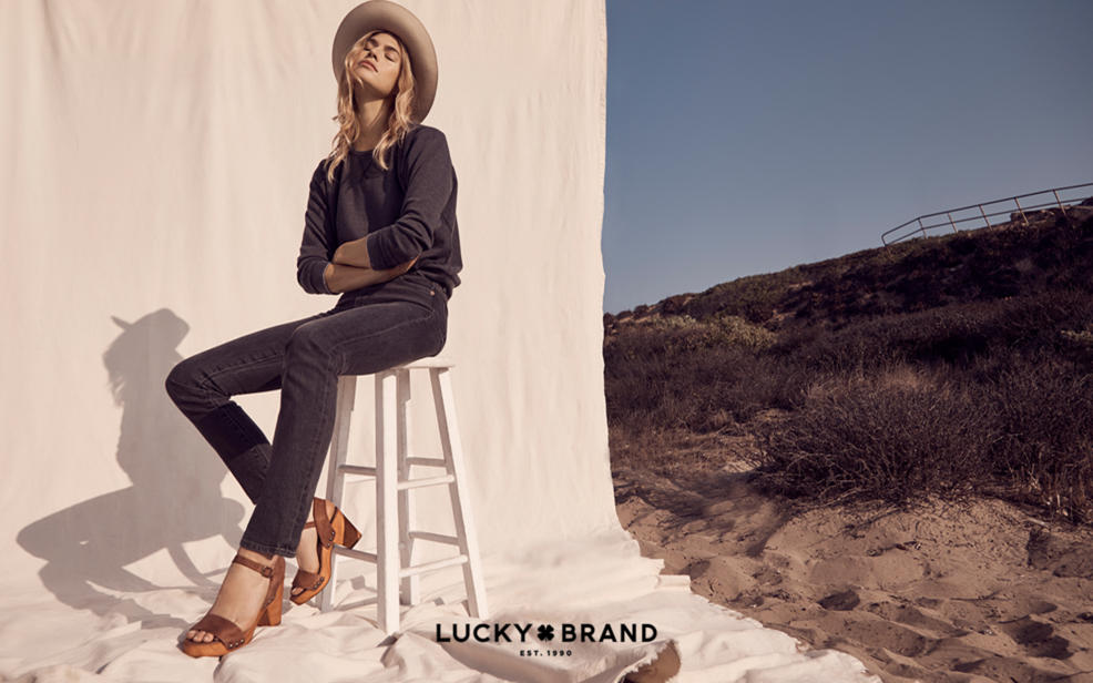 lucky brand established 1990.  a woman in a rimmed hat wears dark jeans and a dark shirt with tall sandals