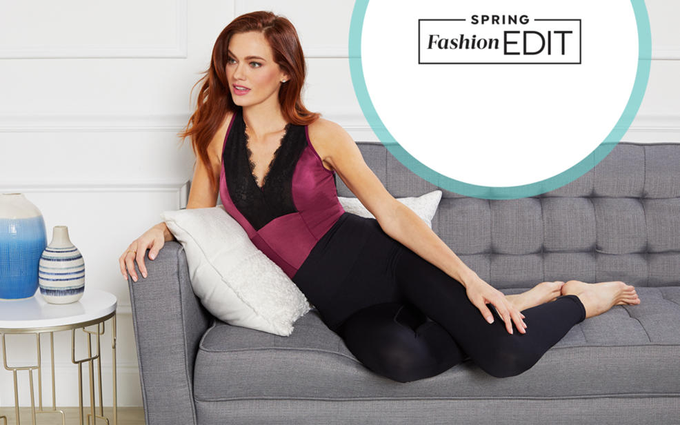 a woman sits on a couch in slimming shapewear