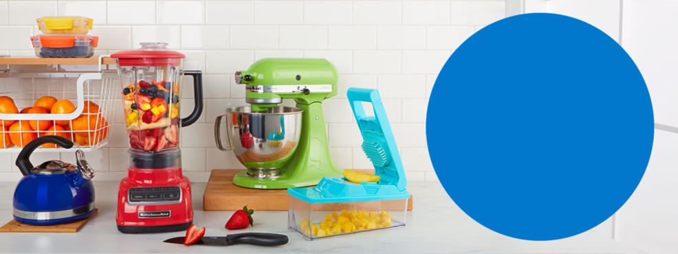 Colorful kitchen products. A blue teapot, red blender, green mixer and a teal mandolin.