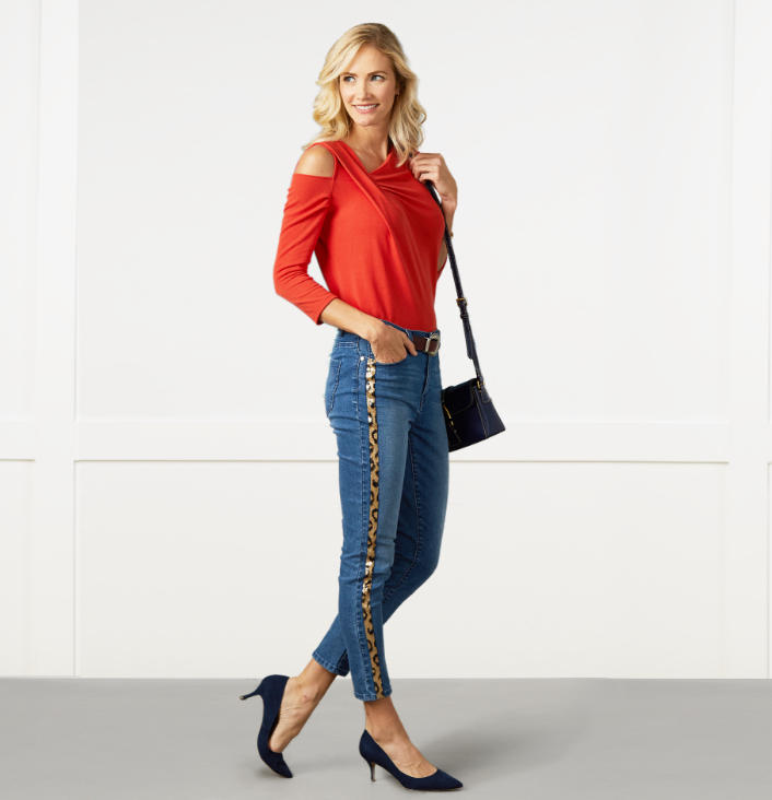 a woman with a pattened top with a floral image and salmon colored jeans.