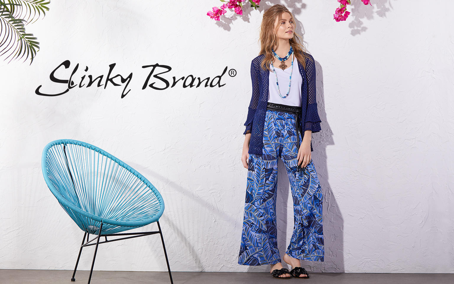 Slinky Brand. A woman in a white top and printed pants wears a blue see through jacket.
